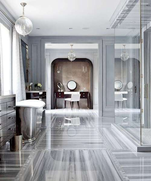 Grey marble bathroom, with shiny floor and large glass shower cubicle