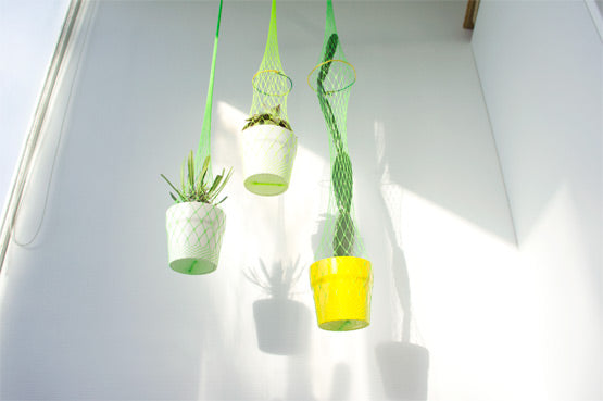 Green fishnet tights used to hang planters on a balcony