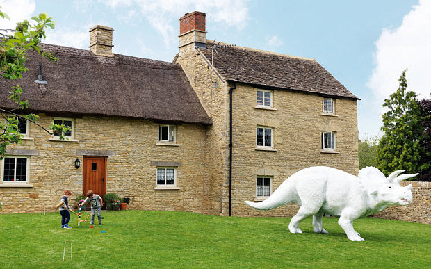 Large white triceratops garden model, with kids playing croquet on the grass
