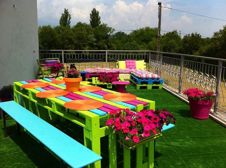 Pallets painting in bright colours and turned into tables, benches and sun loungers
