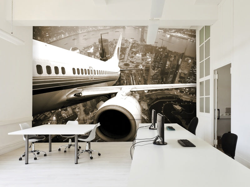White office and reception space with a large sepia wall decal of a planes wing mid flight