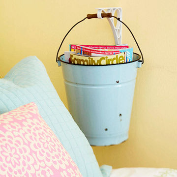 A blue metal bucket used a storage at the side of a bed