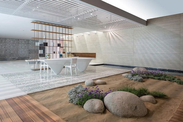 White, cream and grey interior with a sandy beach area with rocks and wild flowers, surrounded by wooden flooring