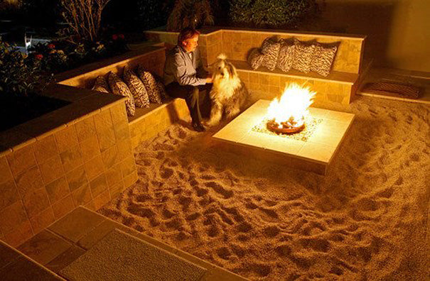 Garden tiled seating area with sand on the floor and square fire pit