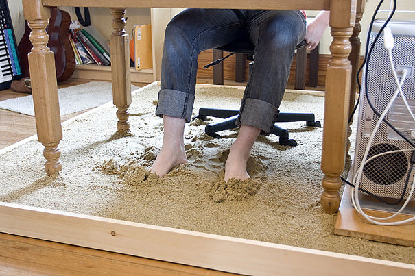An office desk sat on sand, for sitting at the desk barefoot