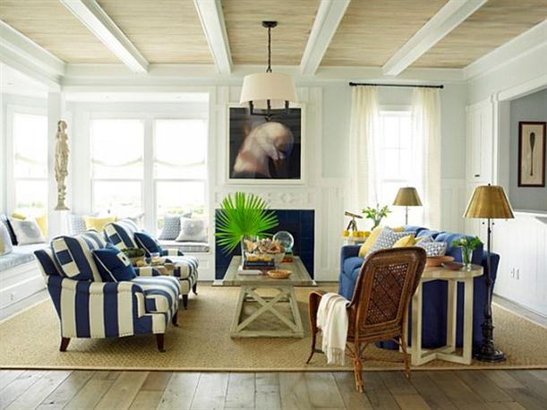 Cream and very light blue beach house interior with cream and dark blue striped seating on a large hessian rug