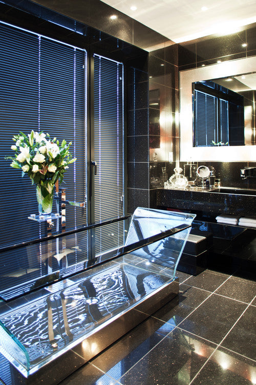 Contemporary glass bathtub in a black tiled bathroom with black venetian blinds