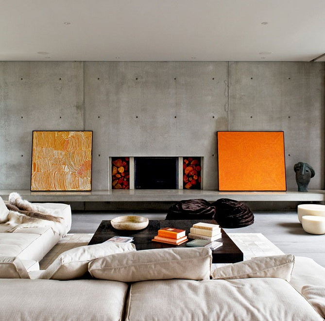 Contemporary urban beach house with exposed concrete walls and floors and orange accessories