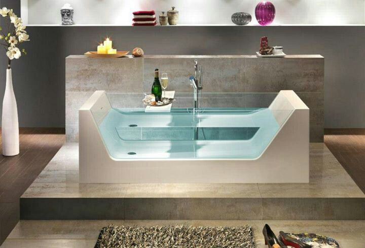 Bathtub with two glass sides that has curved sides which make it look like a booth at a restaurant