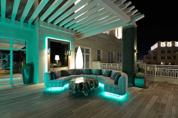 Roof top modern seating area with large semi circle seating area and light blue lighting