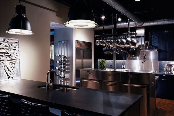 Modern black and cream kitchen area with polished surfaces and lots of silver surfaces and pans