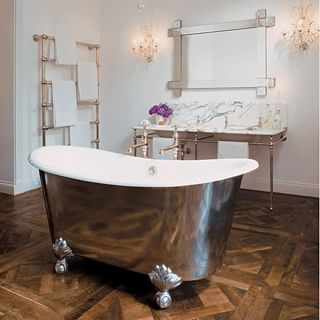 Raised polished metal bathtub and dark wood flooring