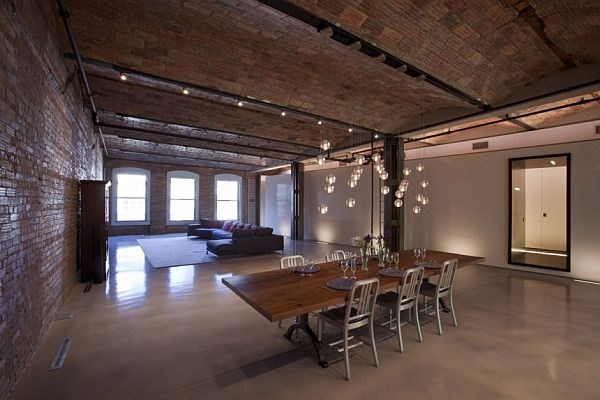 Large industrial living space with with sitting area in the distance and dining table in the foreground