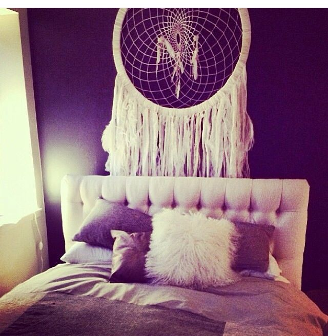 Stylish photo of a bed with cushions and a large dream catcher over the bed