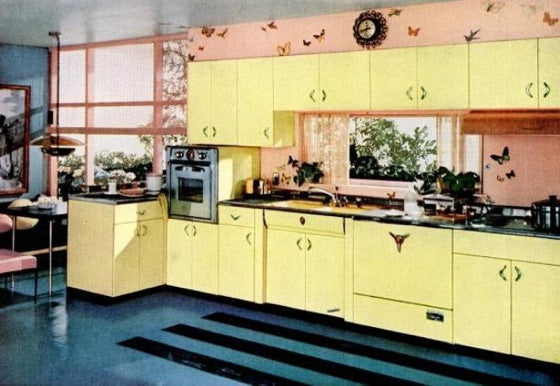 1950s blue floored kitchen with bright yellow kitchen cabinets and a peach tiled wall with butterfly design
