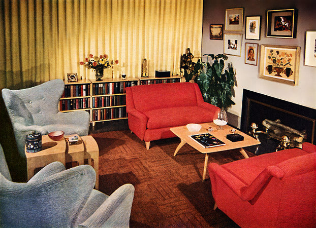 Seventies style living room with stripy textured wall, red two seater chairs facing each other around a small coffee table and two light blue arm chairs