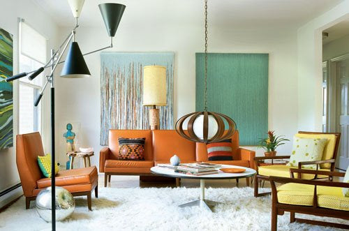 White living room, with white shag pile rug, orange leather sofa and armchair and pendant shaped oval lamp shade suspended quite low from the ceiling