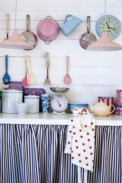 Pastel kitchen accessories and lampshades above a white kitchen counter top