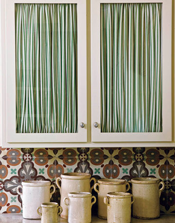 Glass door kitchen units, with green striped curtains behind the glass for privacy