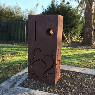 Large rusty metal block stood upright, with an intricate swirling pattern at the base