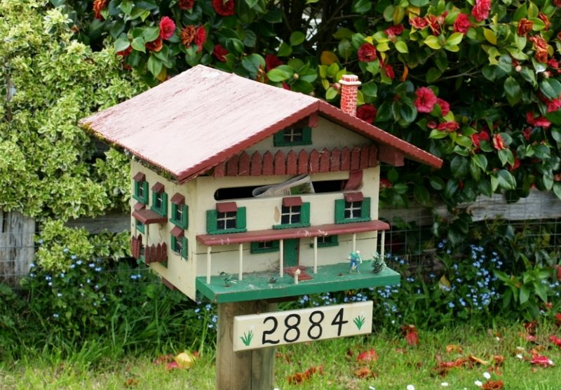 A front garden mailbox, in the shape of a little cream house with red roof