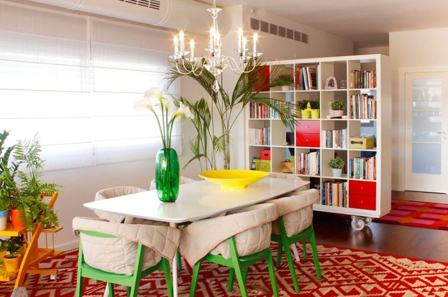 Lovely white and bright dining room with hints of green, yellow and a traditional geometric red rug