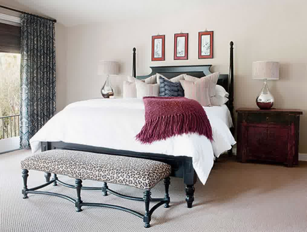 High black bed frame with white bedding, and animal print bench at the foot of the bed