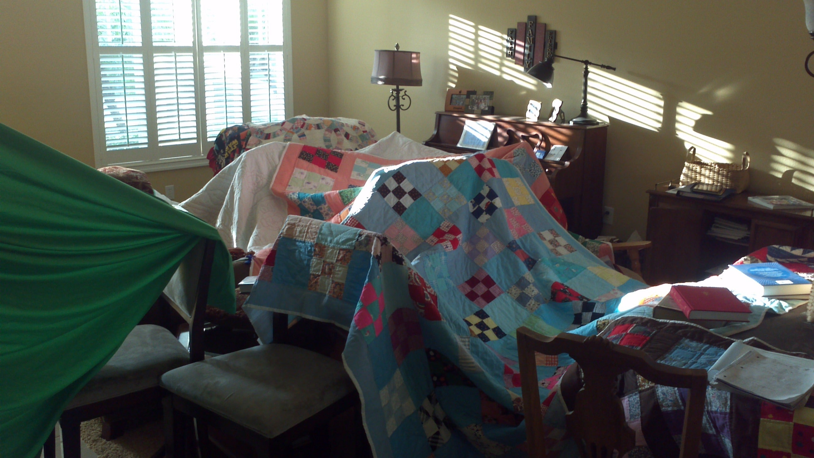 Blanks and throws covering dining room chairs to make a child fort, castle or den