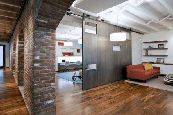 Modern office and living space with dark orange sofa and sliding floor to ceiling industrial door