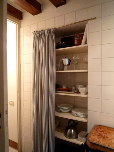 Inset kitchen shelves with a curtain in front to keep them out of sight