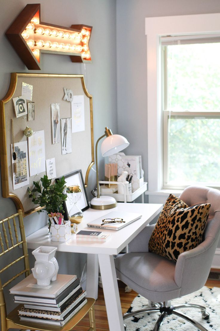 Modern home office with gold accessories, leopard print cushion and arrow decorative light