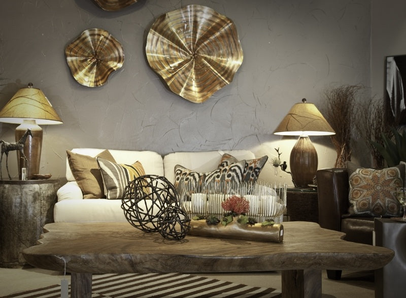 White sofa with funky gold wall art and lampshades, with natural wood coffee table