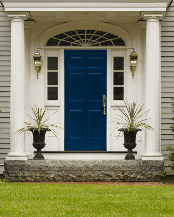 Dakr blue front door, with classy cream surround and decorative pillars on either side
