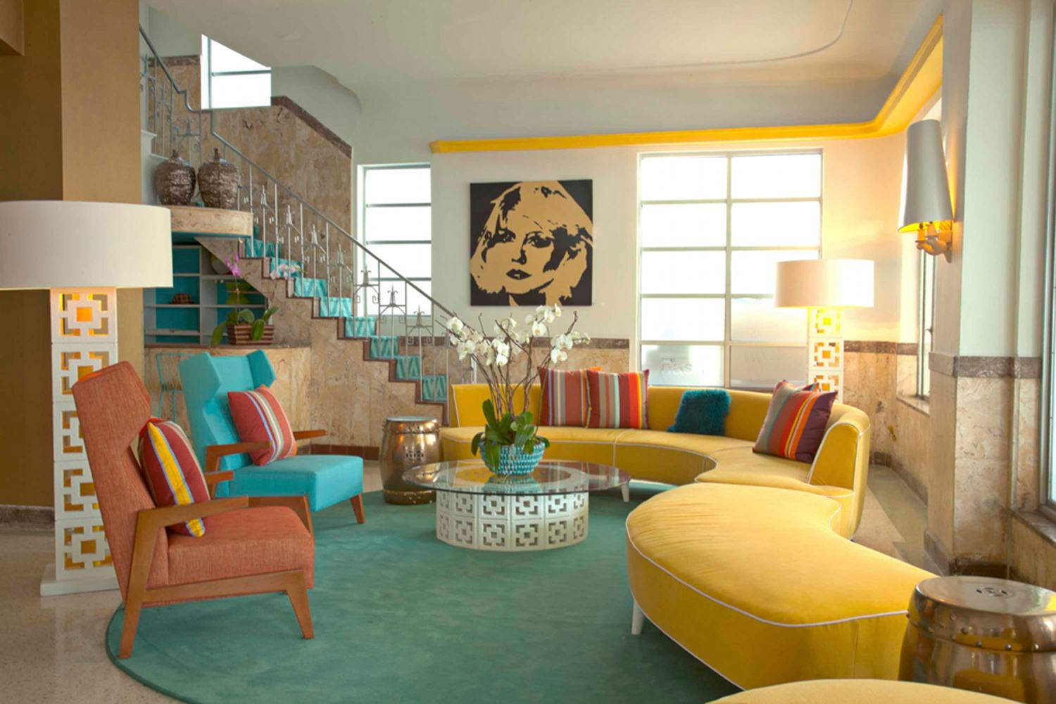 Luxury living room space with a yellow curvey sofa, duck egg blue bean shaped rug and Debbie Harry black and gold pop art wall canvas