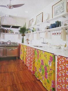 Dark wood floor in a white kitchen with bright yellow and red material used instead of unit doors