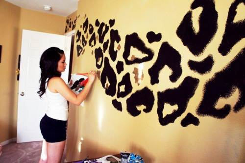 A woman painting a cheetah print on a yellow wall