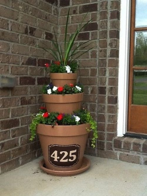 Three different sized plant pots stacked on top of each other, filled with soil and plants coming out of each