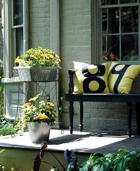 Raised porch at the front of the house, with black wooden bench with one yellow cushion saying 8, the other 9