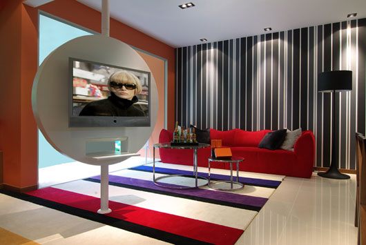 Futuristic style living space with black and white striped wallpaper, red sofa and TV on a rotating circle for position it towards the sofa or towards the kitchen