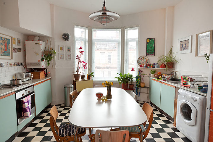 Interior of a cream kitchen with black and white checked floor