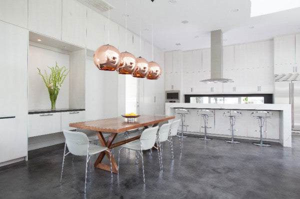 Dark grey flooring in a kitchen with copper lampshades and an all white finish