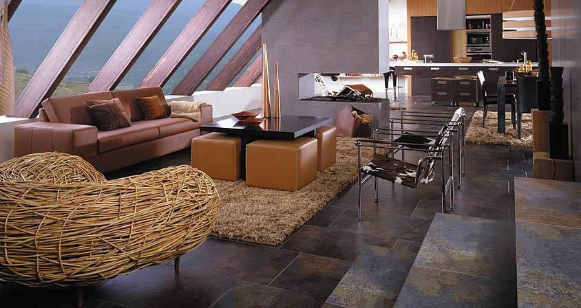 Dark natural stone floor tiles in stylish living room, dining room and kitchen
