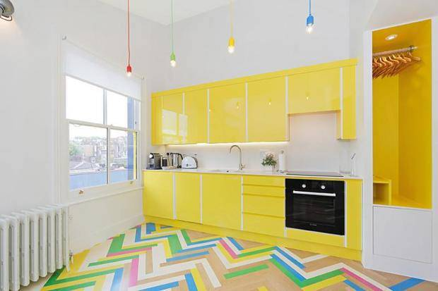 Bright yellow kitchen cabinets, with zigzag bright coloured flooring