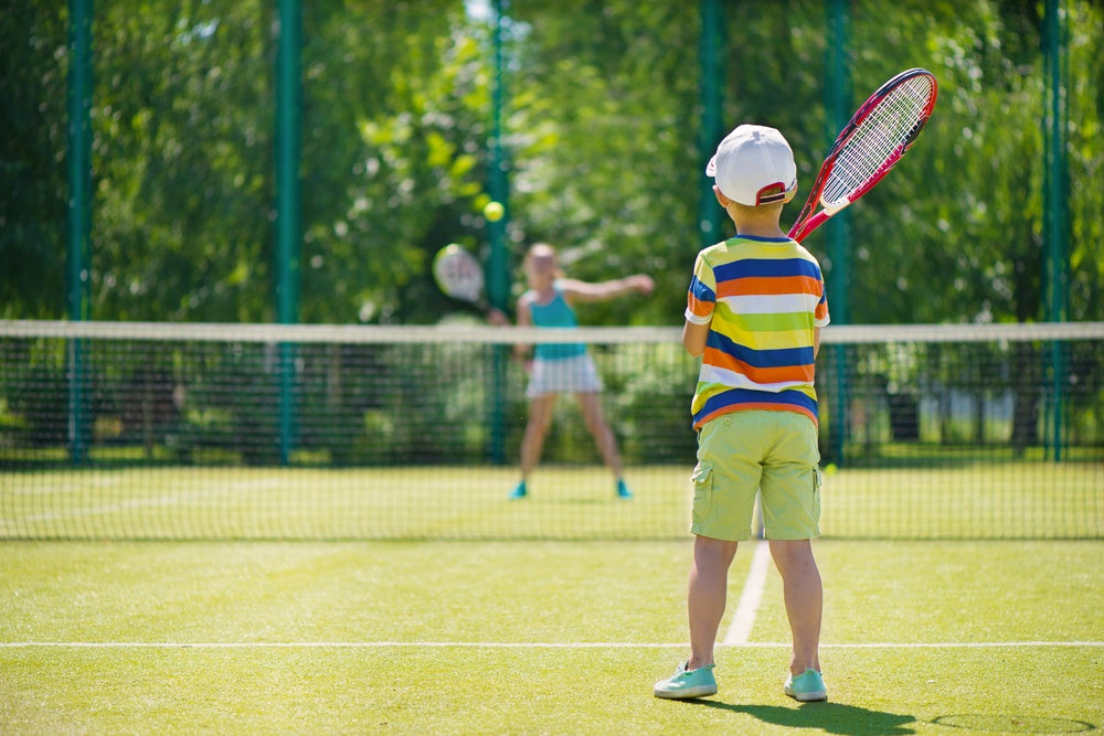 Two children playing tennis on an outdoor faux grass court