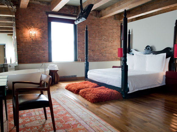 Wooden floors and exposed brick walls in a bedroom with a black bed frame and white bathtub