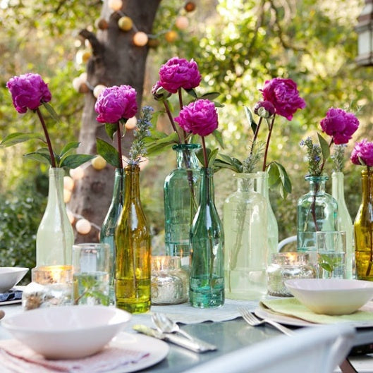 Summer wedding table decor with purple flowers in empty glass bottles