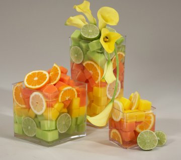 Glass vases filled with melon, kiwi, oranges, lemons and limes