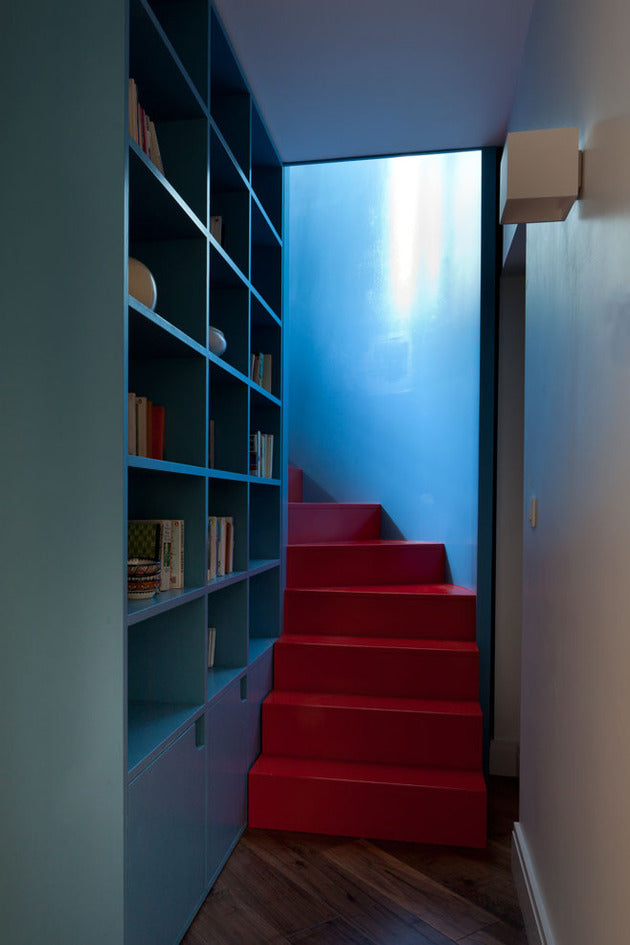 vibrant red staircase with blue walls and shelves
