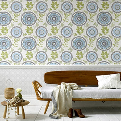 Geometrical wallpaper with a floral blue and green design, above a wooden indoor bench