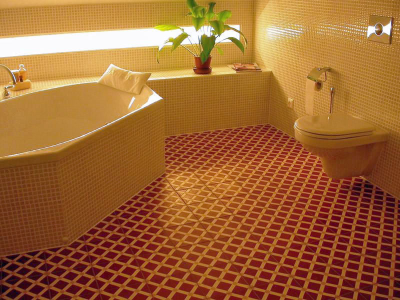 Red and yellow geometric mesh pattern on bathroom tiled floor